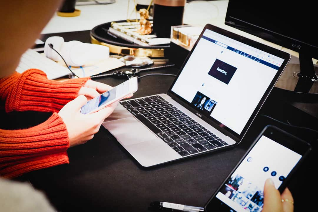 Using tools like a laptop and iPhone to set up successful B2B social media marketing.