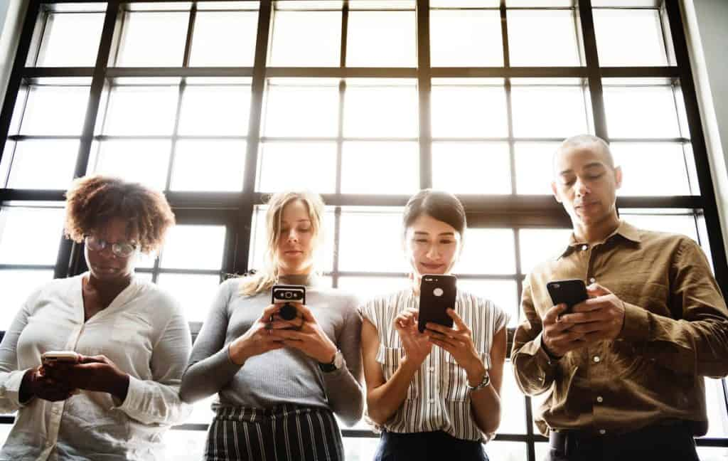 People smiling at their phones to show positive brand awareness through B2B social media marketing.