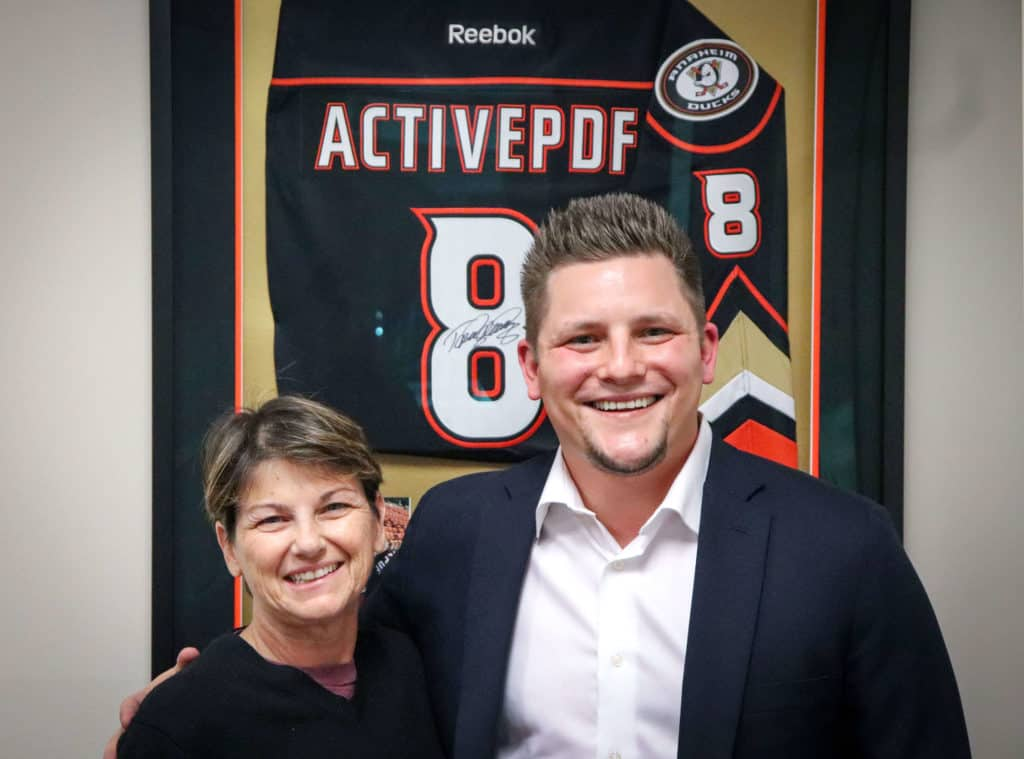Active PDF B2B marketing colleagues in front of their personalized Anaheim Ducks jersey.